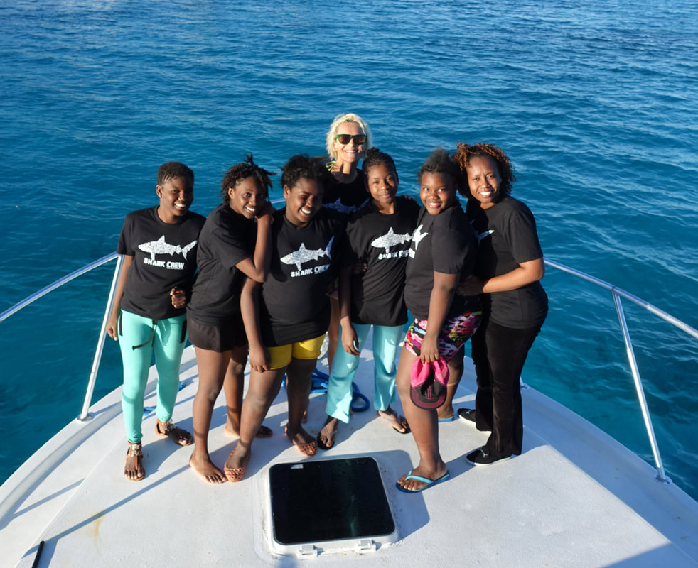 Jillian posing on a boat with female students in the Bahamas